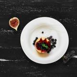 可口蛋糕服务用蓝莓、果酱和薄荷叶 免版税库存照片