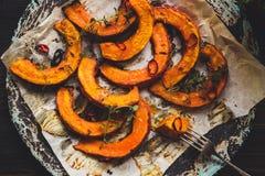 可口被烘烤的南瓜用麝香草和辣椒在木桌上,顶视图 免版税库存图片