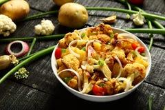 可口被烘烤的土豆和花椰菜 服务在白色碗 库存图片