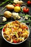 可口被烘烤的土豆和花椰菜 服务在白色碗 库存照片