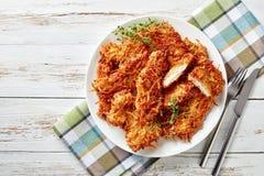 可口被磨碎的土豆涂上了并且油炸了在一块板材的炸猪排在与餐巾、叉子和刀子的一张土气白色木桌上, 库存图片