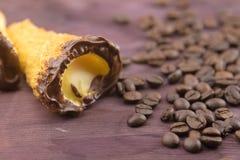可口西西里人的cannolo cannellino甜点用在咖啡豆附近的酥皮点心榛子 免版税库存图片