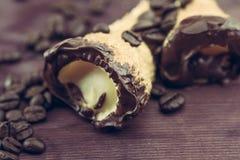可口西西里人的cannolo cannellino甜点用在咖啡豆附近的酥皮点心榛子 免版税库存照片