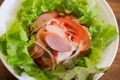 可口辣香肠用在白色板材的菜沙拉 库存照片