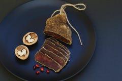 可口辣鲜美芳香生涩与红色石榴种子和核桃在黑陶瓷板材在黑暗的背景 库存图片