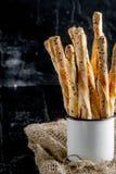 可口面包棒grissini 意大利语的开胃菜 木黑暗的背景和粗麻布在金属老式杯子 免版税库存照片