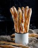 可口面包棒grissini 意大利语的开胃菜 木黑暗的背景和粗麻布在金属老式杯子 库存照片