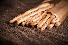 可口面包棒grissini 意大利语的开胃菜 木黑暗的背景和粗麻布 免版税库存图片