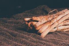 可口面包棒grissini 意大利语的开胃菜 木黑暗的背景和粗麻布 库存照片