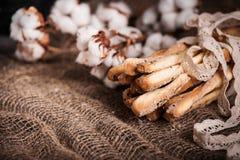 可口面包棒grissini 意大利语的开胃菜 棉花和自然亚麻制鞋带木黑暗的背景和粗麻布花  库存图片