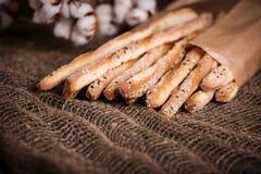 可口面包棒grissini 意大利语的开胃菜 棉花木黑暗的背景和粗麻布花  免版税库存图片