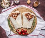 可口面卷饼用肉、豆和菜在切板和一块餐巾用西红柿和大蒜在木rusti 图库摄影