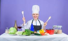 可口食谱概念 食家主菜食谱 烹调是她的爱好 烹调健康的食物 帽子和围裙的女孩 免版税库存照片