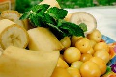 可口香蕉和樱桃李子在五颜六色的板材开胃菜, 免版税库存图片