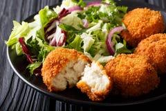 可口鱼开胃菜:在添面包的鳕鱼蛋糕用新鲜的沙拉 免版税库存照片