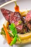可口鹿肉牛排用在白色板材,专属餐馆的产品摄影的土豆饲料和菜 库存图片