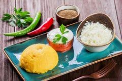 可口麦片粥-玉米粥碎玉米粥用山羊乳干酪、黄油和酸性稀奶油在木背景 健康的食物 库存照片