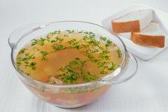可口,开胃浅褐色的汤用在一块透明板材的草本 在一块白色板材的面包 水平的框架 库存图片