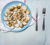 可口,水多的鸡胸脯用草本,夏南瓜,在一把白色餐巾刀子的一块蓝色在木土气backg的板材和叉子 免版税库存图片