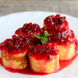 可口绉纱滚动用红浆果调味汁在一块白色板材 油煎的绉纱卷食谱 美味的复活节早餐想法 库存照片