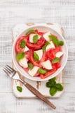 可口caprese沙拉用成熟蕃茄和无盐干酪乳酪与新鲜的蓬蒿离开 烹调意大利语的食品成分 免版税图库摄影