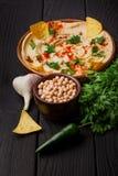 可口hummus延长了一块黑褐色木板材 在黑桌背景的明亮的开胃菜构成 库存图片