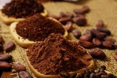 可可粉、可可粒和咖啡豆在木板材在粗麻布 免版税库存照片