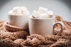 可可粉或咖啡用蛋白软糖在一个白色杯子有褐色的编织了冬天围巾 抽象空白背景圣诞节黑暗的装饰设计模式红色的星形 免版税库存图片