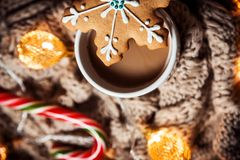 可可粉或咖啡用蛋白软糖在一个白色杯子有褐色的编织了冬天围巾 抽象空白背景圣诞节黑暗的装饰设计模式红色的星形 免版税图库摄影