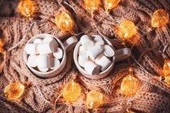 可可粉或咖啡用蛋白软糖在一个白色杯子有褐色的编织了冬天围巾 抽象空白背景圣诞节黑暗的装饰设计模式红色的星形 免版税库存照片
