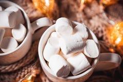 可可粉或咖啡用蛋白软糖在一个白色杯子有褐色的编织了冬天围巾 抽象空白背景圣诞节黑暗的装饰设计模式红色的星形 库存图片
