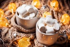 可可粉或咖啡用蛋白软糖在一个白色杯子有褐色的编织了冬天围巾 抽象空白背景圣诞节黑暗的装饰设计模式红色的星形 库存照片