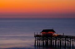 可可粉有美好的日落的海滩码头 库存图片