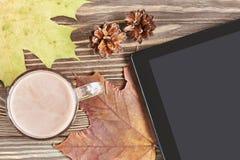 可可粉杯子、秋叶、锥体和片剂个人计算机 免版税图库摄影