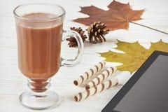 可可粉杯子、秋叶、锥体和片剂个人计算机 免版税库存图片