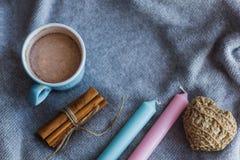 可可粉蓝色蜡烛肉桂条编织了心脏灰色被编织的背景 免版税图库摄影