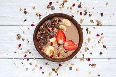 可可粉香蕉蛋白质有巧克力格兰诺拉麦片、草莓和石榴种子的圆滑的人碗 免版税库存图片