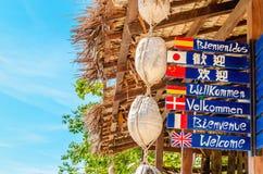 可喜的迹象用在海滩的不同的语言 免版税库存图片