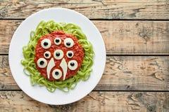 可怕万圣夜妖怪绿色意粉面团用假血液西红柿酱 库存图片