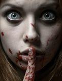 可怕女孩和万圣夜题材:一个疯狂的女孩的画象有一张血淋淋的面孔的在演播室 免版税图库摄影