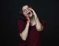 可怕女孩和万圣夜题材:一个疯狂的女孩的画象用一只血淋淋的手在黑暗的背景的演播室盖面孔,  免版税图库摄影