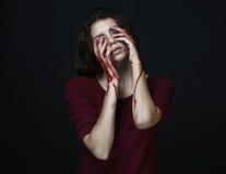 可怕女孩和万圣夜题材:一个疯狂的女孩的画象用一只血淋淋的手在黑暗的背景的演播室盖面孔,  免版税库存照片