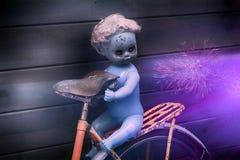 可怕有黑色的鬼魂塑料玩偶撕毁在神秘的夜自然背景的自行车 免版税图库摄影