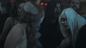 可怕玩具动物半截面罩舞蹈的女孩在夜总会万圣夜党的人群 股票录像