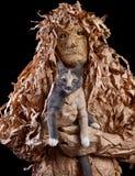 可怕生物在手边收留在黑背景的一只猫 库存图片