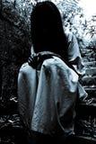 可怕的妇女坐台阶 库存图片