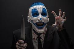 可怕的小丑和万圣夜题材:一套黑衣服的疯狂的蓝色小丑与一把刀子在的黑暗的背景隔绝的他的手上 免版税库存照片