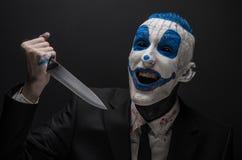 可怕的小丑和万圣夜题材:一套黑衣服的疯狂的蓝色小丑与一把刀子在的黑暗的背景隔绝的他的手上 库存图片
