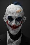 可怕的小丑和万圣夜题材:在黑暗的背景隔绝的黑衣服的疯狂的可怕的蓝色小丑在演播室 免版税库存图片