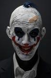 可怕的小丑和万圣夜题材:在黑暗的背景隔绝的黑衣服的疯狂的可怕的蓝色小丑在演播室 免版税库存照片